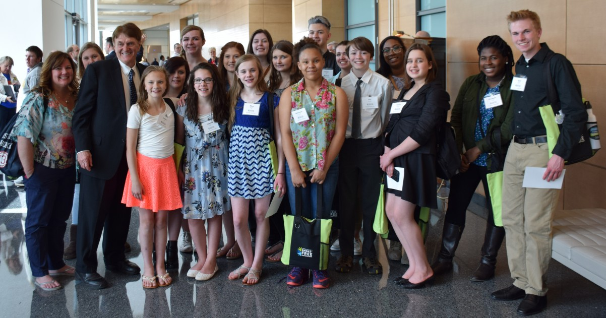 Youth from John Glenn and Tartan High take a photo with Sen. Charles Wiger.