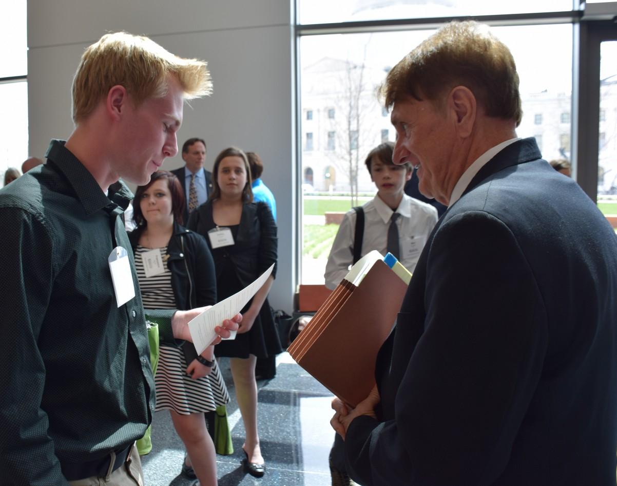 Tartan High SADD member Ryan Lenard talks with Sen. Charles Wiger about the harms of tobacco.